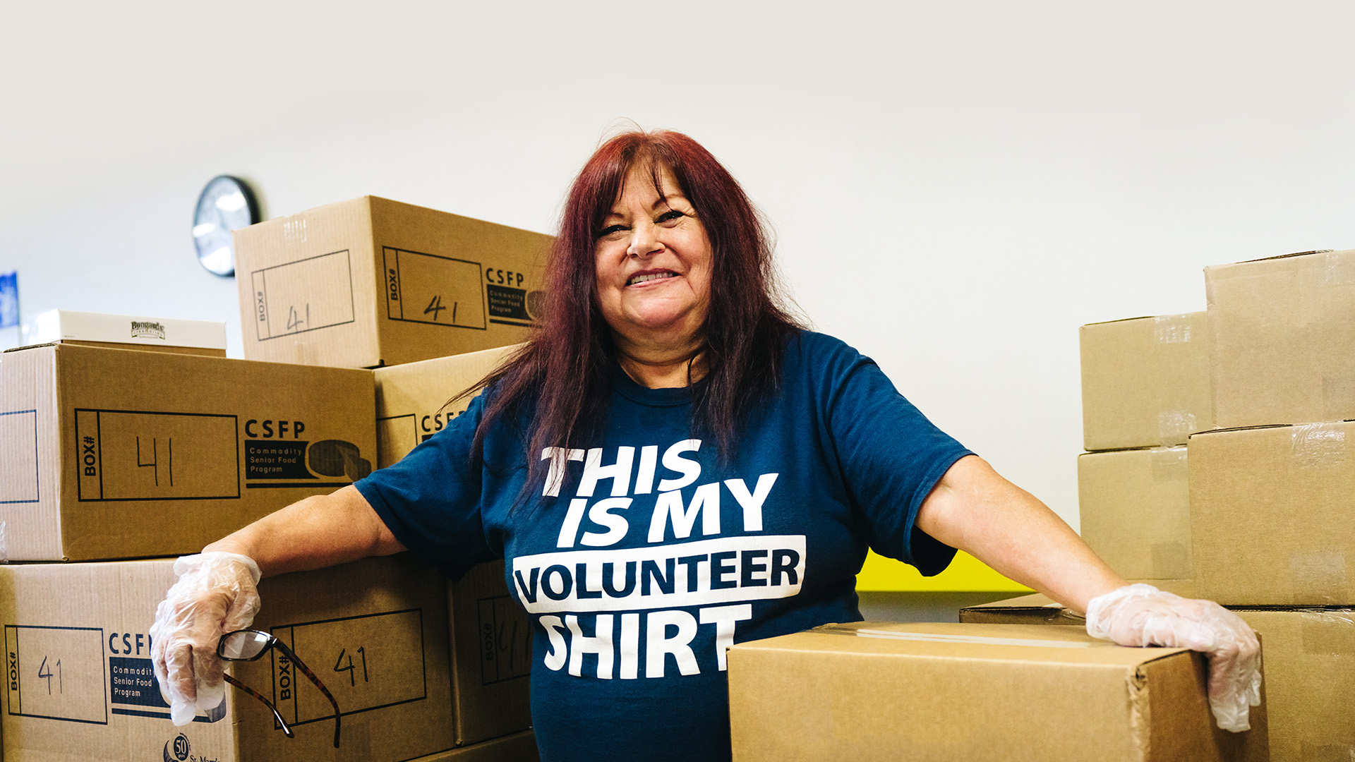 Volunteer helping sort donation boxes of food.